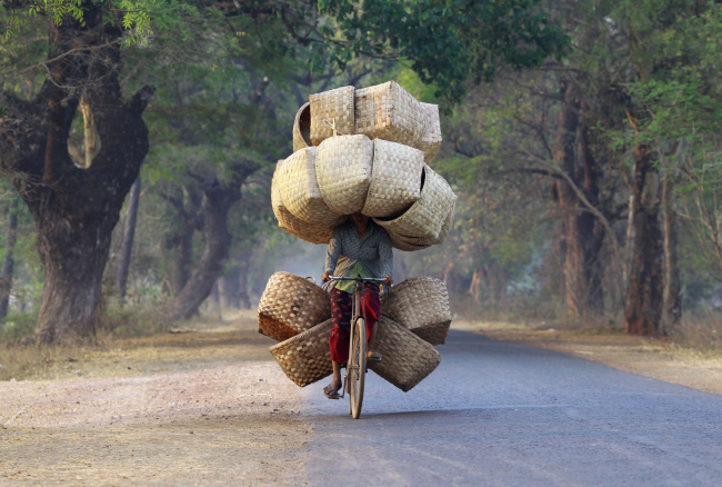 A woman cycles as she carries baskets to sell in a market near Lapdaung mountain in Sarlingyi township, March 13, 2013. REUTERS/Soe Zeya Tun (MYANMAR - Tags: SOCIETY TPX IMAGES OF THE DAY) ) - RTR3EWWQ